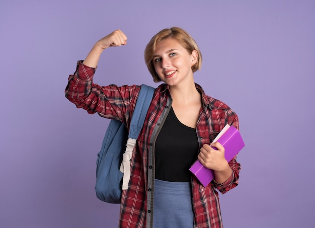 Lächelndes junges slawisches studentenmädchen, das rucksack trägt, spannt bizeps an, hält buch und notizbuch