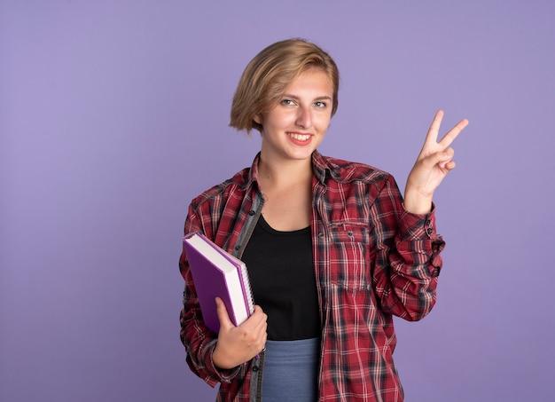 Lächelndes junges slawisches studentenmädchen gestikuliert sieghandzeichen hält buch und notizbuch