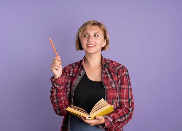 Lächelndes junges slawisches studentenmädchen hält bleistift und buch, das auf die seite schaut