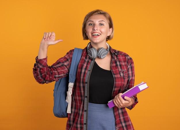 Lächelndes junges slawisches studentenmädchen mit kopfhörern, das rucksack trägt, hält buch- und notizbuchpunkte an sich selbst