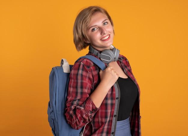 Lächelndes junges slawisches studentenmädchen mit kopfhörern, das rucksack trägt, steht seitlich