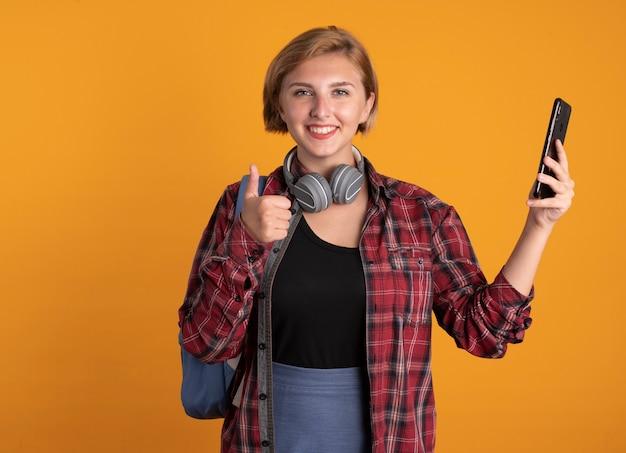 Lächelndes junges slawisches studentenmädchen mit kopfhörern, das rucksackdaumen nach oben trägt und telefon hält