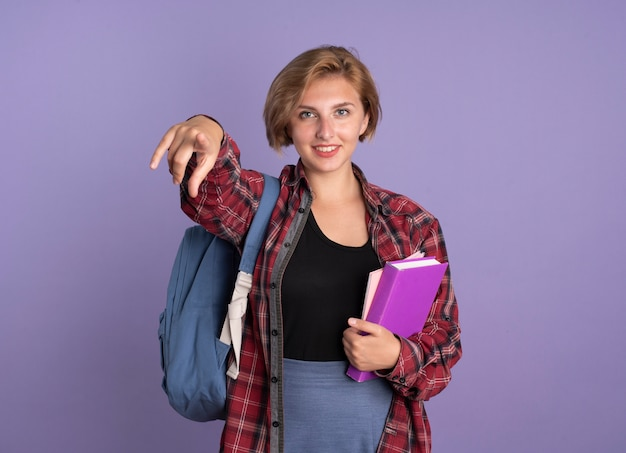 Lächelndes junges slawisches studentenmädchen mit rucksack, das buch und notizbuch hält und auf die kamera zeigt