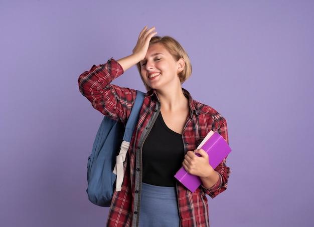 Lächelndes junges slawisches studentenmädchen mit rucksack hält buch und notizbuch legt die hand auf die stirn