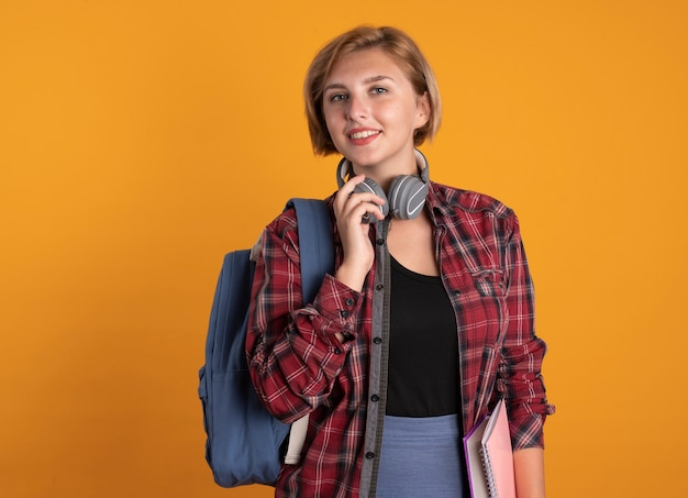 Lächelndes junges slawisches studentenmädchen mit rucksack hält kopfhörer um den hals around