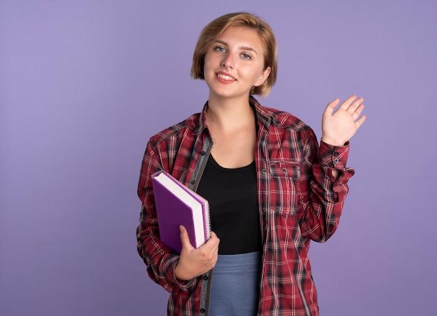 Lächelndes junges slawisches studentenmädchen steht mit erhobener hand hält buch und notizbuch