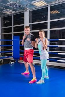 Lächelndes junges sportliches paar im sportbekleidungstraining im regulären boxring in einer turnhalle