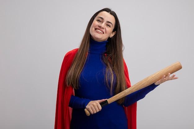 Lächelndes junges superheldenmädchen, das baseballschläger lokalisiert auf weiß hält