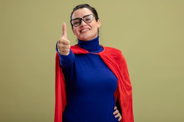 Lächelndes junges superheldenmädchen, das brillen trägt, zeigt daumen oben lokalisiert auf olivgrünem hintergrund
