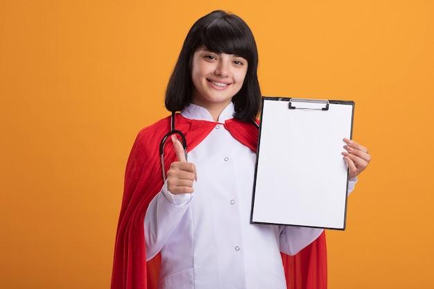 Lächelndes junges superheldenmädchen, das stethoskop mit medizinischem gewand und umhang hält, das klemmbrett hält, das daumen oben auf orange wand lokalisiert zeigt
