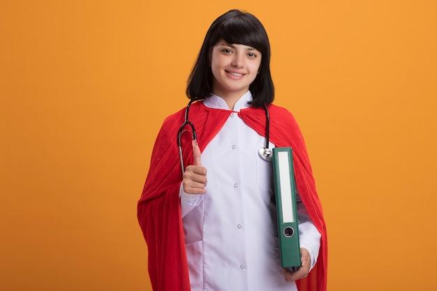 Lächelndes junges superheldenmädchen, das stethoskop mit medizinischem gewand und umhang hält ordner hält und daumen oben zeigt