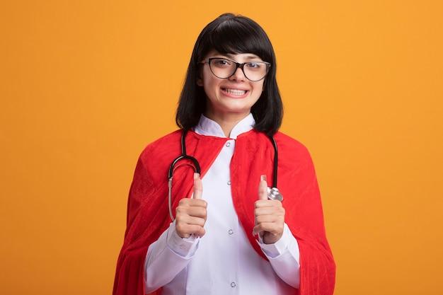 Lächelndes junges superheldenmädchen, das stethoskop mit medizinischem gewand und umhang mit brille trägt, die daumen oben zeigt