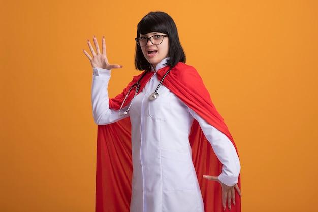 Lächelndes junges superheldenmädchen, das stethoskop mit medizinischem gewand und umhang trägt, der robotertanz tut