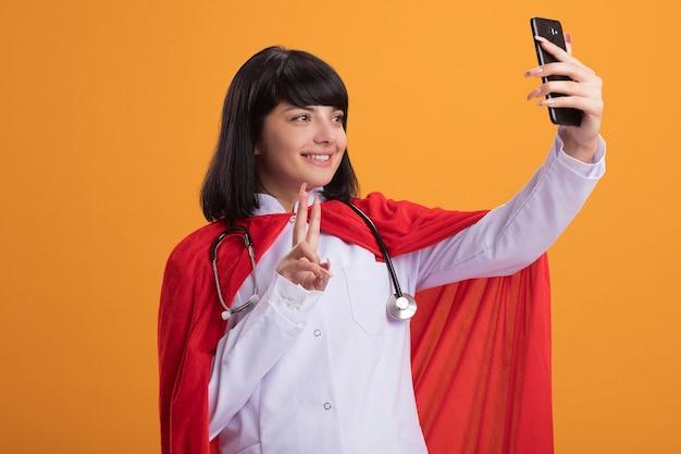 Lächelndes junges superheldenmädchen, das stethoskop mit medizinischem gewand und umhang trägt, nehmen ein selfie, das friedensgeste zeigt