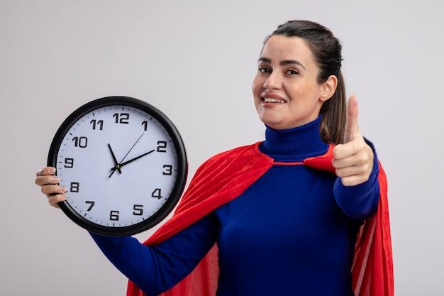 Lächelndes junges superheldenmädchen, das wanduhr hält daumen lokalisiert auf weißem hintergrund