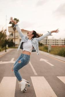 Lächelndes junges weibliches schlittschuhläufertanzen mit rollschuh auf straße
