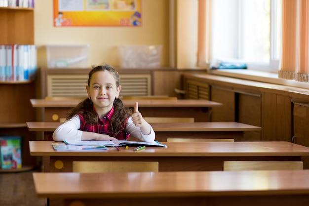 Lächelndes kaukasisches mädchen, das am schreibtisch im klassenzimmer sitzt und daumen herauf geste zeigt. das junge vorschulmädchen glückliche schülerin