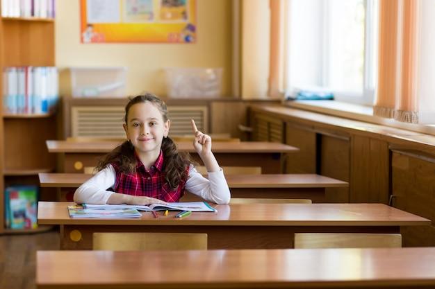 Lächelndes kaukasisches mädchen, das am schreibtisch im klassenzimmer sitzt und ihren finger hält