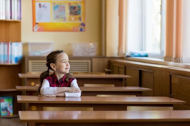 Lächelndes kaukasisches mädchen, das am schreibtisch im klassenzimmer sitzt und im fenster schaut.