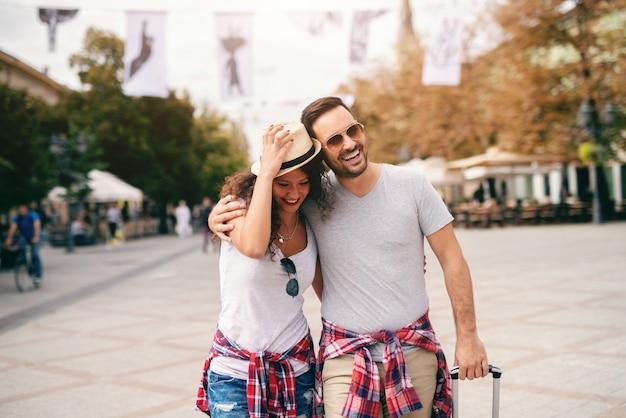Lächelndes kaukasisches paar, das auf der allee geht und umarmt. frau, die hut hält, während mann gepäck hält. reisekonzept.