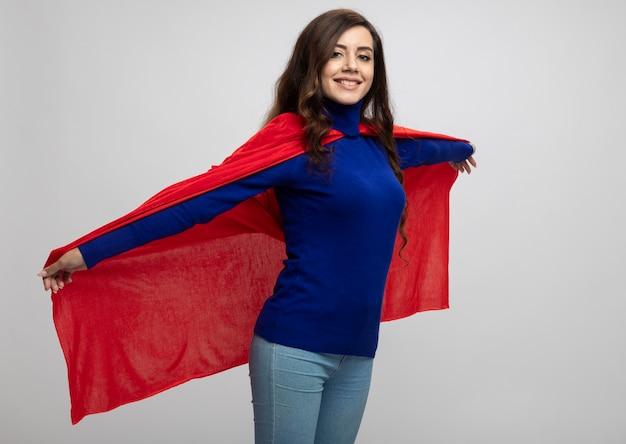 Lächelndes kaukasisches superheldenmädchen hält roten umhang auf weiß