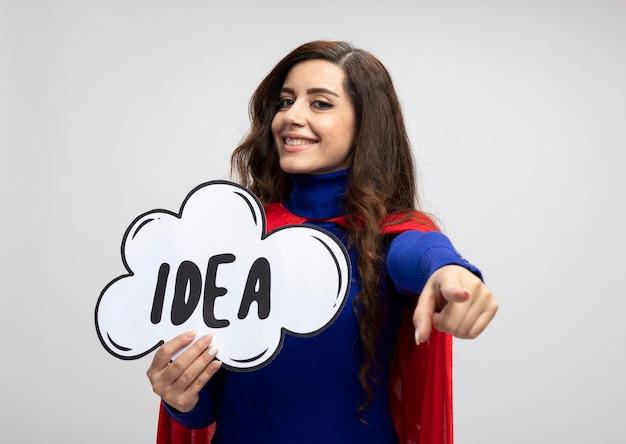 Lächelndes kaukasisches superheldenmädchen mit rotem umhang hält ideenblase