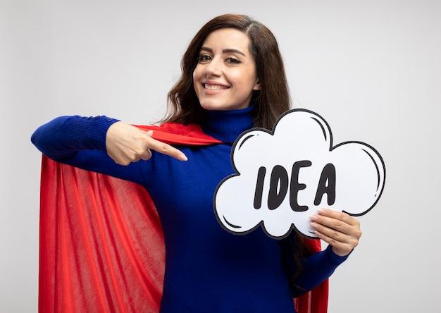 Lächelndes kaukasisches superheldenmädchen mit rotem umhang hält und zeigt auf idee
