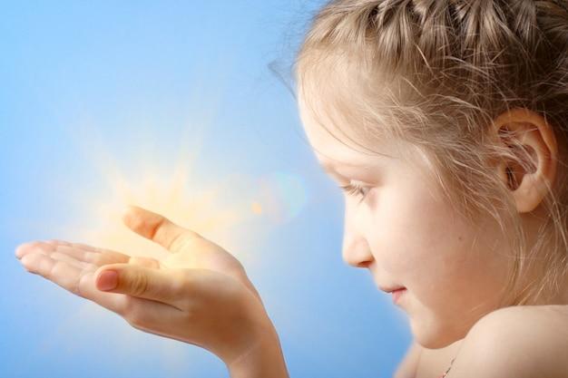 Lächelndes kind, das eine sonne an ihren händen auf einem hintergrund des blauen himmels hält