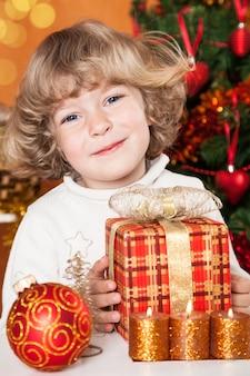 Lächelndes kind, das geschenk gegen weihnachtsbaum mit dekorationen hält