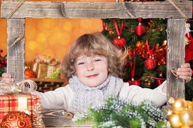 Lächelndes kind, das holzrahmen gegen weihnachtsbaum mit dekorationen hält