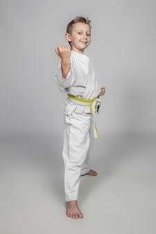 Lächelndes kind, das kampfkunst übt, einen judogi tragend.