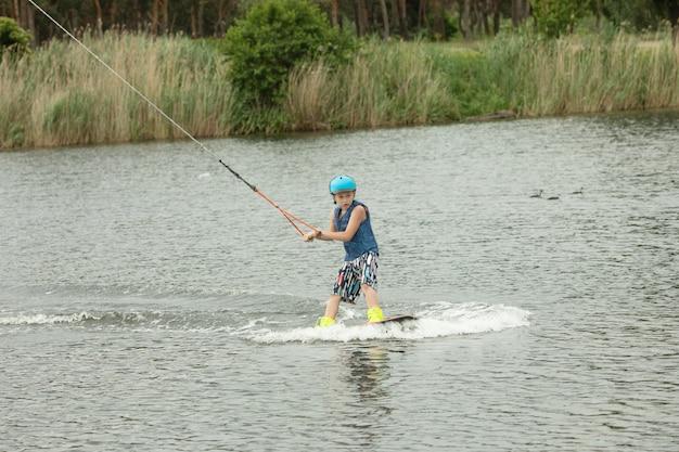 Lächelndes kind, das wake-board lernt.