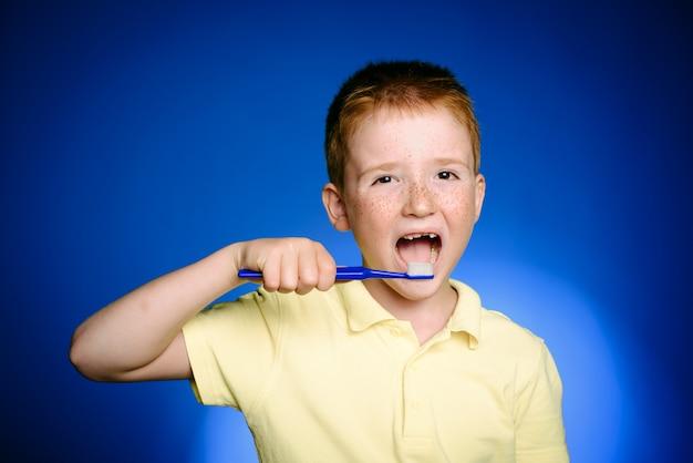 Lächelndes kind des kleinen jungen mit der zahnbürste in der hand lokalisiert auf blauem hintergrund. kindergesundheitspflege, kinderzahnhygiene. kleiner junge mit zahnbürste. shirt-design, gesundheit, mundhygiene.