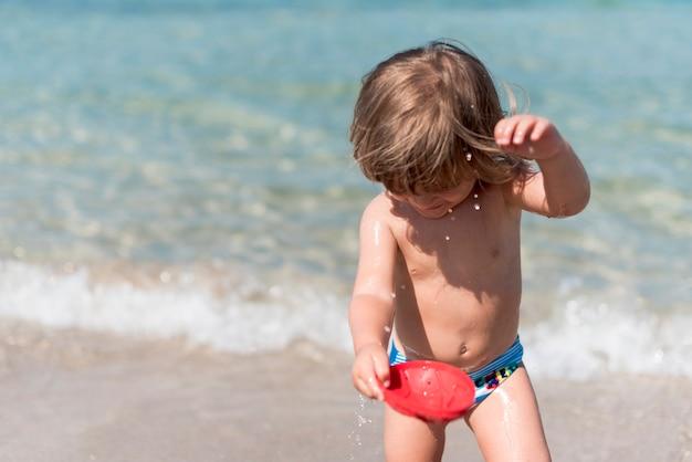 Lächelndes kind des mittleren schusses, das mit wasser am strand spielt