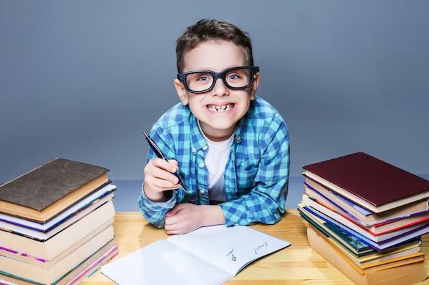 Lächelndes kind in gläsern, die hausaufgaben am schreibtisch machen. junger schüler im klassenzimmer