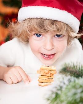 Lächelndes kind in weihnachtsmütze, das weihnachtsplätzchen isst
