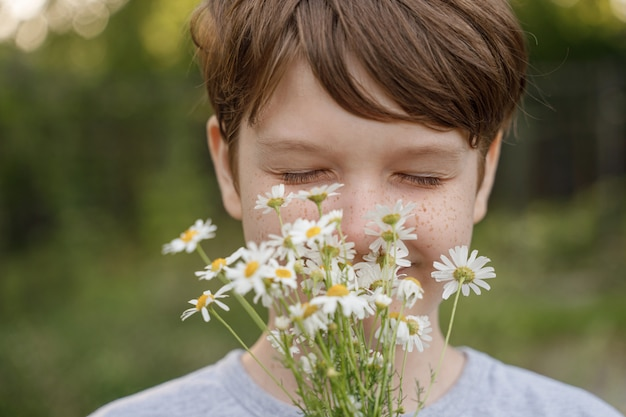 Lächelndes kind mit einem blumenstrauß des weißen gänseblümchens.