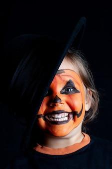 Lächelndes kind mit einem schwarzen hut und einem kürbismuster auf seinem gesicht, halloween, nahaufnahme