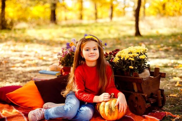 Lächelndes kind mit korb der roten äpfel, die im herbstpark sitzen