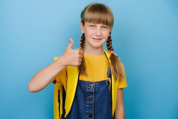 Lächelndes kindergrundschulmädchen mit gelbem rucksack, der daumen nach oben zeigt, lokalisiert über blauem farbhintergrund im studio. glücklicher blonder kinderstudent, der die freiheit feiert und die beste bildungswahl empfiehlt