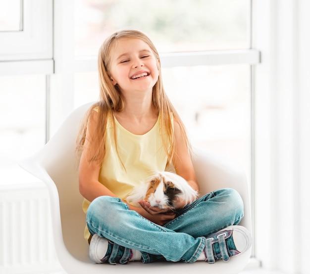 Lächelndes kindermädchen, das nettes meerschweinchen hält