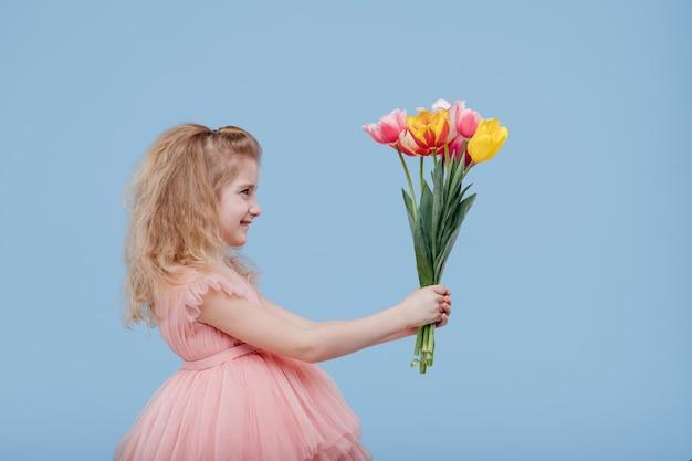 Lächelndes kindermädchen im rosa kleid mit frühlingsblumen in der hand, lokalisiert auf blauer wand, seitenansicht