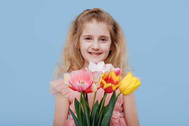 Lächelndes kindermädchen im rosa kleid mit frühlingsblumen in der hand, lokalisiert auf blauer wand