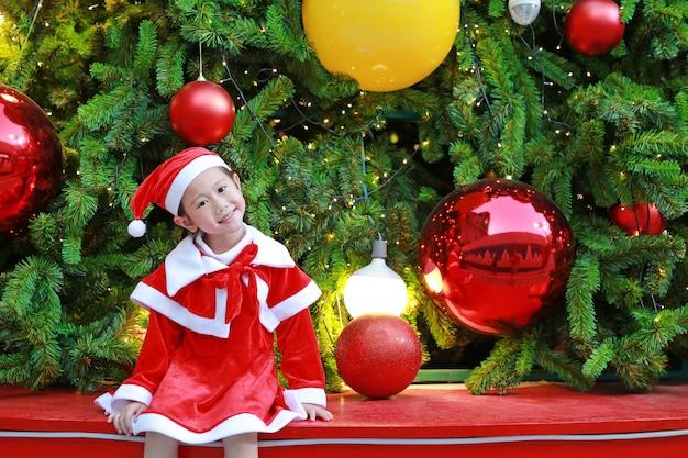 Lächelndes kindermädchen in sankt-kostüm mit weihnachtshintergrund. frohe weihnachten und ein glückliches fest