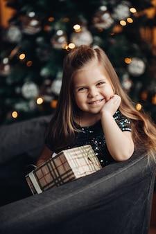 Lächelndes kindermädchen mit langen gesunden haaren, die festliches weihnachtsgeschenk auf weihnachtsbaum halten.