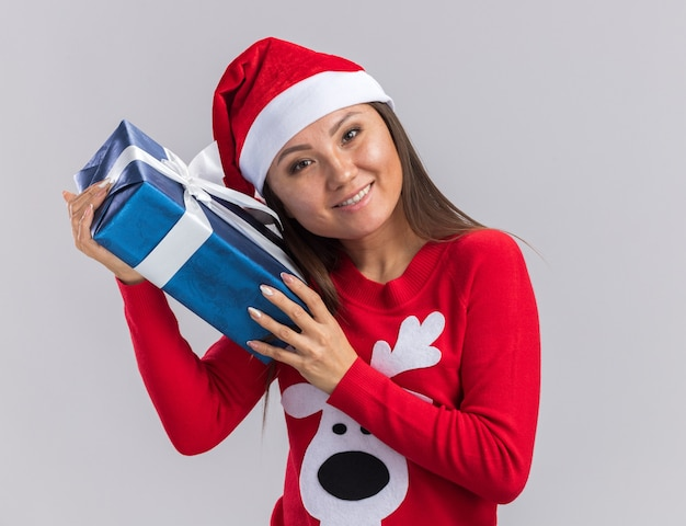 Lächelndes kippendes junges asiatisches mädchen des kippkopfes, das weihnachtshut mit pullover hält, der geschenkbox um gesicht lokalisiert auf weißem hintergrund hält
