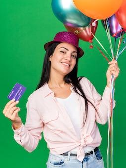 Lächelndes, kippendes junges schönes mädchen mit partyhut, das luftballons mit kreditkarte hält, isoliert auf grüner wand