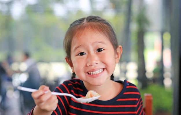 Lächelndes kleines asiatisches kindermädchen, das am café sitzt und frühstück isst