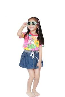 Lächelndes kleines asiatisches kindermädchen, das ein blumenmustersommerkleid und eine sonnenbrille lokalisiert auf weißem hintergrund trägt
