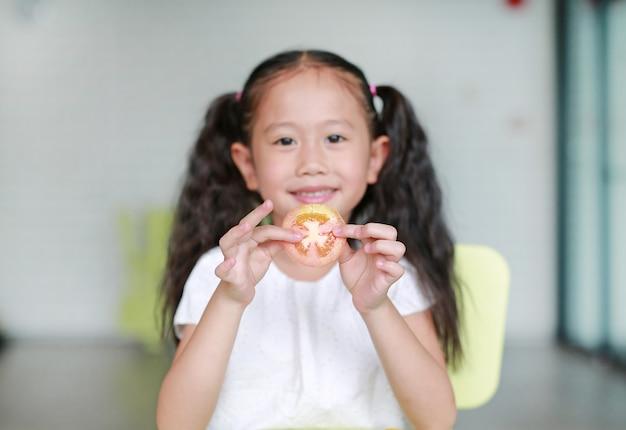 Lächelndes kleines asiatisches kindermädchen, das ein stück geschnittene tomate hält. kind, das gesundes nahrungsmittelkonzept isst. konzentrieren sie sich auf tomaten in kinderhänden.
